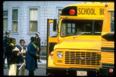 AfricanAmerican students being guarded by police boarding school bus headed for newly integrated high school in South Boston