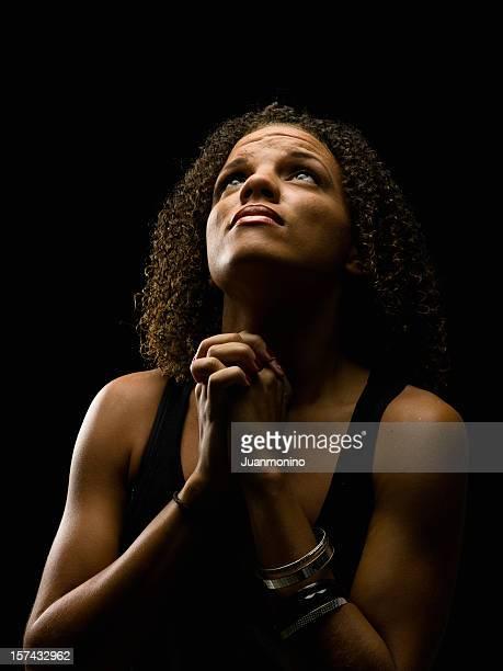 African-American woman praying upwards on black background.