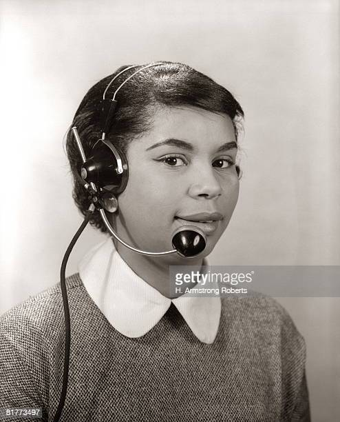African-American Woman Wear Headset As Telephone Operator, Office Receptionist At Switchboard.