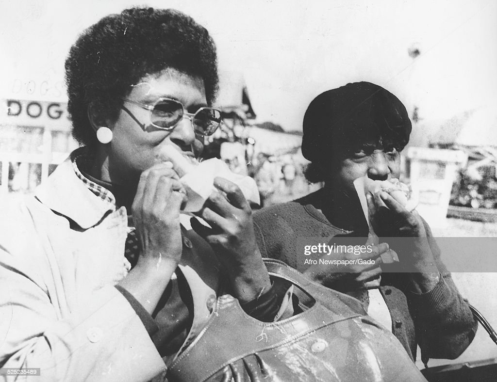 African-American women wearing Afro haircut, eating a meal at a State fair, Richmond, Virginia, 1964. Original Caption Reads: ' Olivia Dyson and Castoria Austin of Norfolk; foot-long hot dog.'