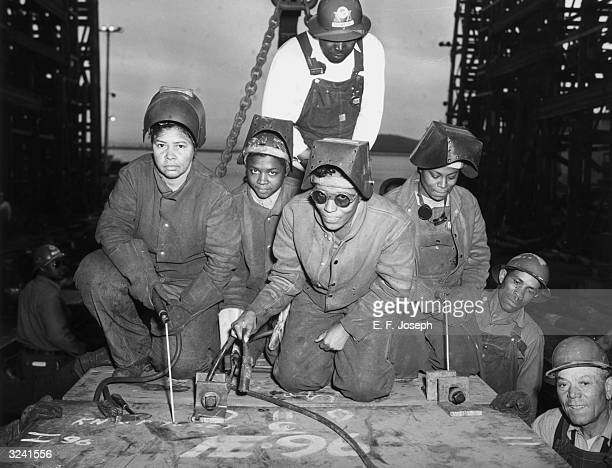 AfricanAmerican women welders kneel in coveralls and hold tools as they prepare to work on SS 'George Washington Carver' World War II Richmond...