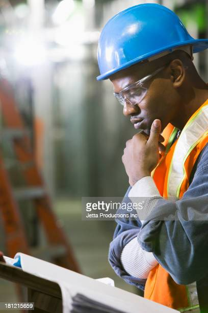 African-American worker reading blueprints on site