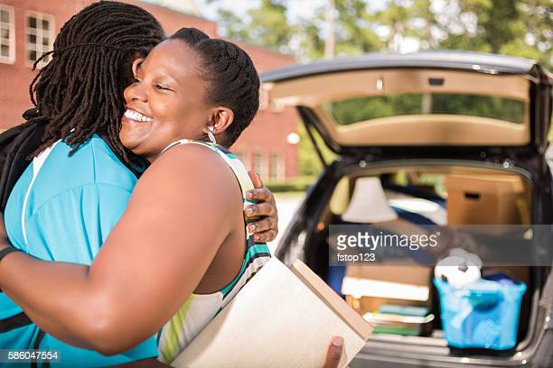 African-descent boy moves into college and hugs mom goodbye.