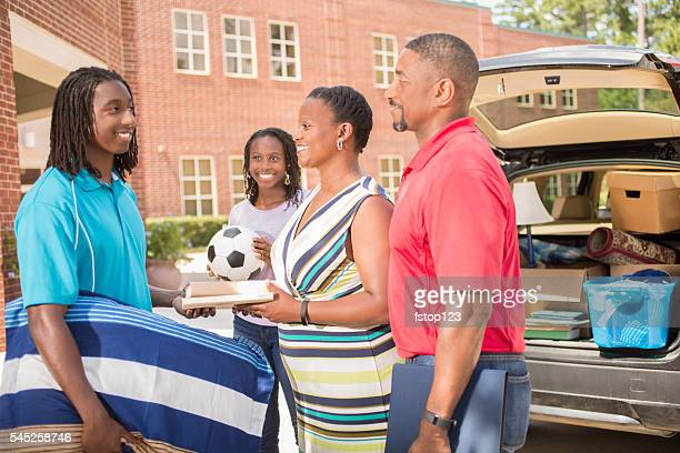 African-descent boy moves into college. Packed car, family.  School campus.