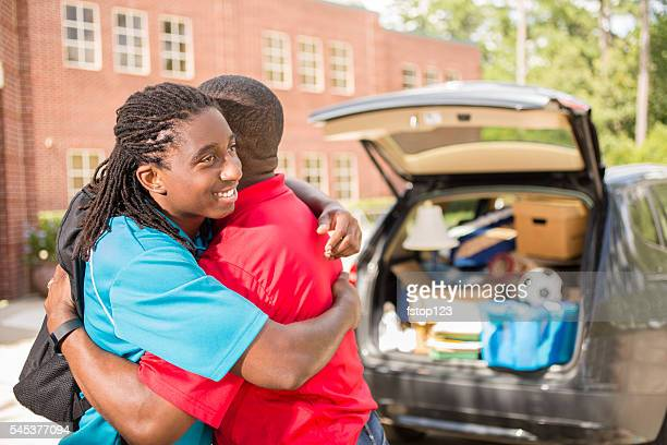 African-descent boy moves into college. Packed car, father. School campus.