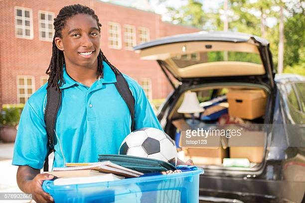 African-descent boy moves into college. Packed car.  School campus.