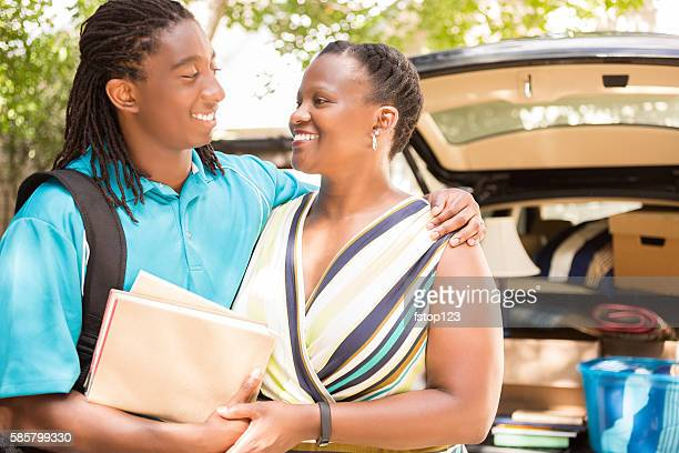 African-descent boy moves off to college and hugs mom goodbye.
