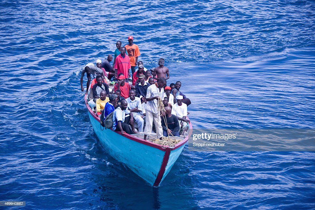 Africans in an overloaded boat : Stock Photo