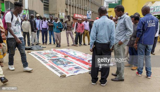 Africans stand next to an election poster warning against the election of the incumbent President Uhuru Kenyatta Street scene in Nairobi capital of...