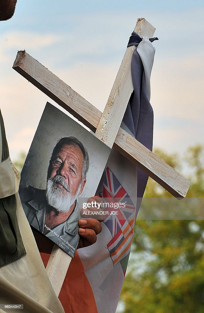 A Afrikaner Resistance Movement (AWB) member holds a picture of AWB leader Eugene Terre'Blanche and an AWB flag tied to a cross during his funeral at a church in Ventersdorp on April 9, 2010. Grim-faced South African far-righters gathered to mourn slain leader Eugene Terre'Blanche with heavily armed police on alert after his killing reopened racial wounds. Six days after the Afrikaner Resistance Movement (AWB) leader was hacked and bludgeoned to death at his farm in the sparse North West province, 1,000 sombre supporters packed a local church for his funeral.