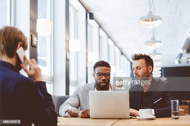 Afro amerikanische und kaukasischen Männer mit laptop in den pub