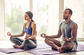 Beautiful Afro American couple in sports clothes is meditating sitting in lotus position on mat while doing yoga at home