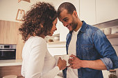 Beautiful Afro American couple is drinking coffee, looking at each other and smiling while resting in kitchen