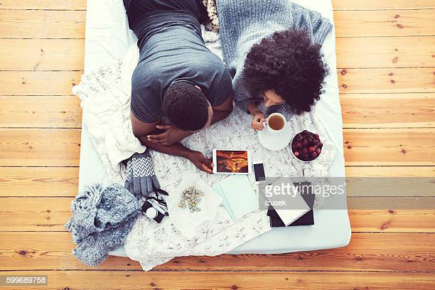 Afro american couple lying on bed and using digital tablet