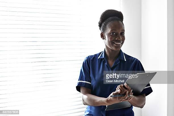 Afro americano enfermera con portapapeles en el hospital