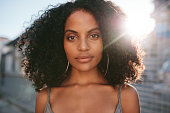 Close up portrait of beautiful young african woman with curly hair. Afro american female standing outdoors.