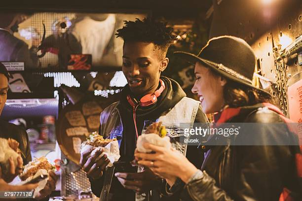 Afro american guy eating burger with his female friend