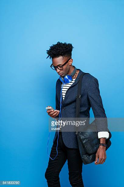 Afro american guy in fashionable outfit, using smart phone