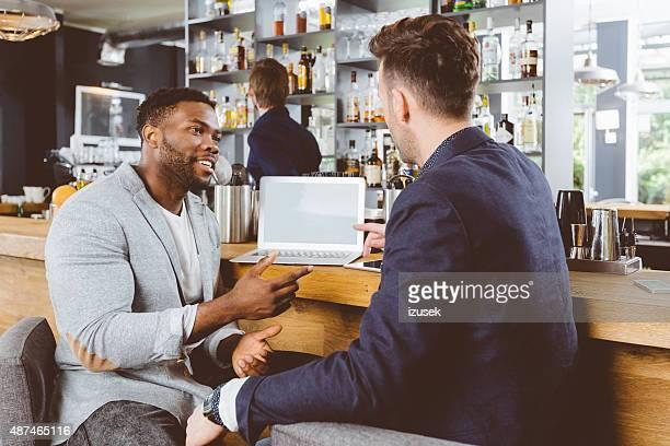 アフリカ系アメリカ人男性が話し、同僚のパブ、ノートパソコンを使う