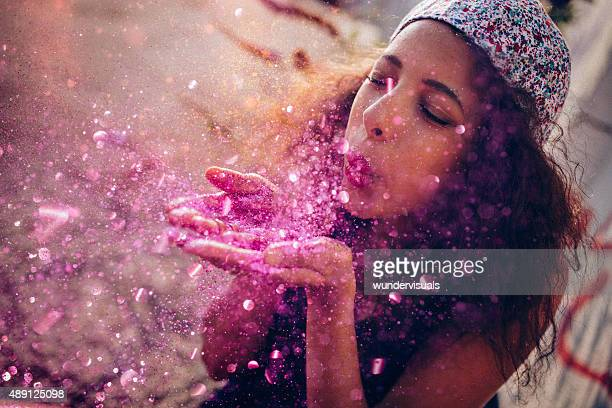 Afro American teen girl blowing pink sparkling glitter outdoors