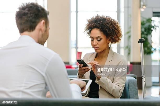 Afro amerikanische Frau mit Smartphone in der hotel lobby