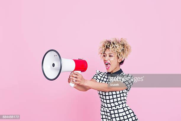 Afro American young woman shouting into megaphone