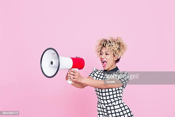 Afro-américaine jeune femme criant en mégaphone