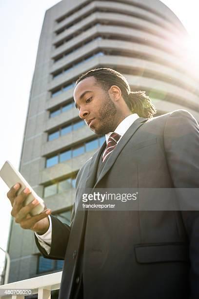アフロのスマートフォンを使用してビジネスの男性の街