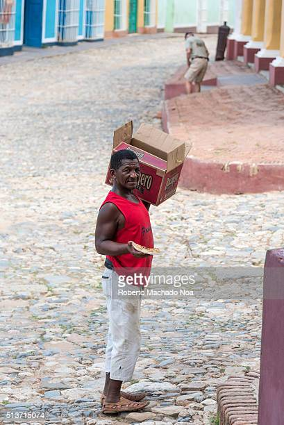 Afro Caribbean man selling homemade pizzas in the streets He transports the food in a Bucanero Beer box that carries in his shoulder