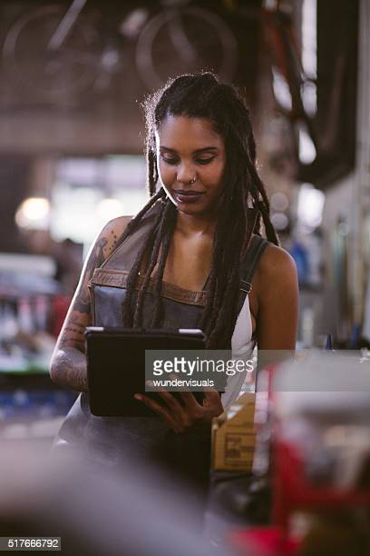 Afro craftswoman using a digital tablet in a workshop