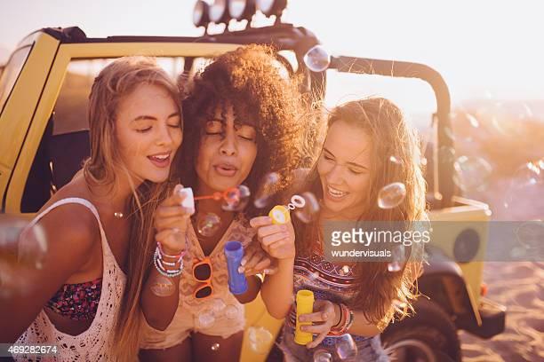 Afro menina e amigos mandar bolhas na praia