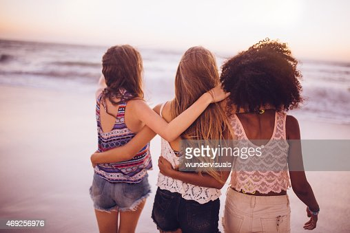 Afro girl and friends walking closely on the beach together