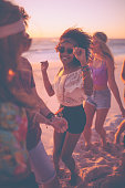 Afro girl dancing with friends at a beachparty