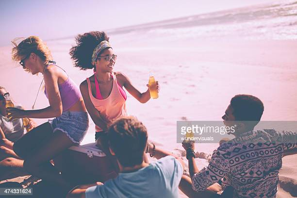 Afro girl drinking beer with friends at a summer beachparty