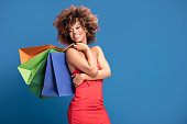 African american woman holding colorful shopping bags, posing on blue background. Girl with big smile wearing red dress enjoying shopping sales.
