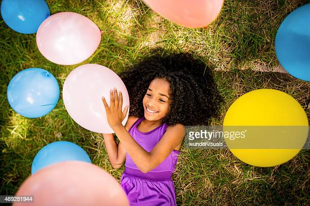 Afro girl lying down with colourful balloons on grass
