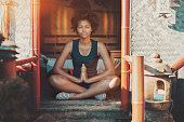 Charming young Brazilian girl with African curly hair has reached nirvana during meditation and aura around her head appeared; black teenage female making yoga exercises while sitting in Asian pagoda