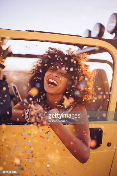 Afro girl on a road trip throwing confetti