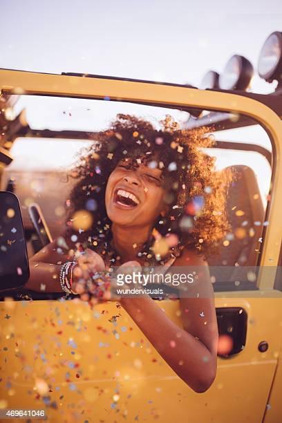 Afro-Mädchen auf einem road trip werfen Konfetti