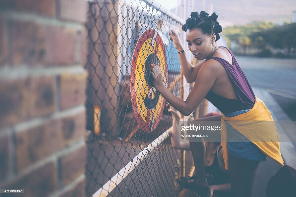 Afro girl trying to illegally climb a fence