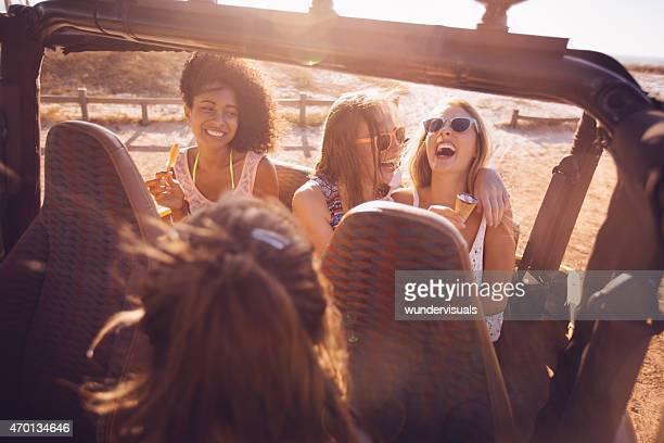 Afro-Mädchen mit Freunden essen Eis am Strand