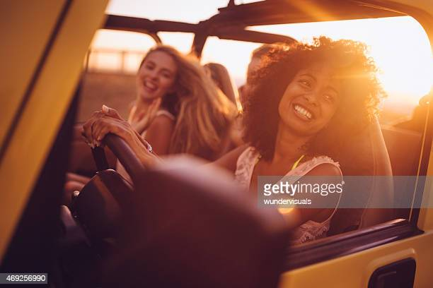 Afro girl with friends on a road trip at sunset