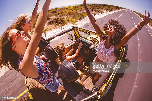 Afro girl with friends standing excitedly on a road trip