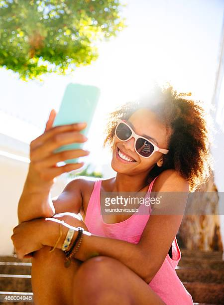 Afro haired girl taking selfie on smartphone