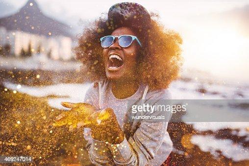 Afro slip a vita bassa ragazza ridere ecstatically e lanciare glitter oro