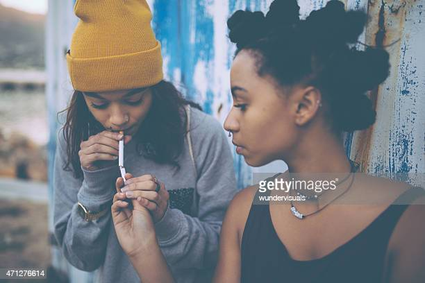 Afro teen lighting a cigarette for her grungy girl friend