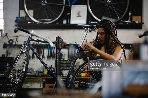 Afro Frau Fahrrad Mechaniker recpairing dem Fahrrad in Ihren Workshop