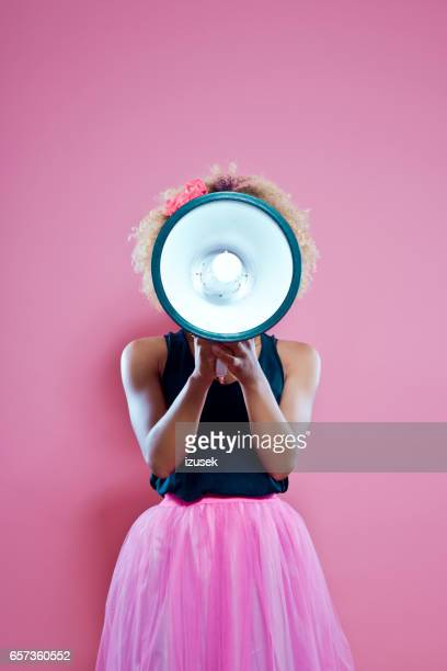 Afro woman holding screaming into megaphone