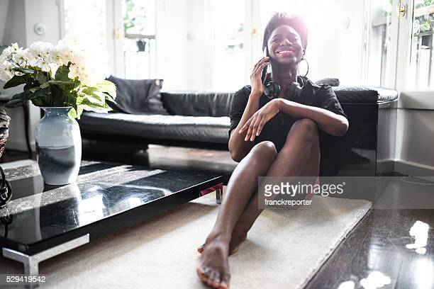 Afro mulher falando no telefone, na sala de estar