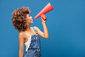 Smiling beautiful young African American woman with curly afro hair screaming by red megaphone.